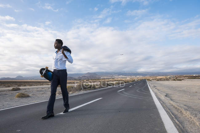 Spain, Tenerife, young businessman with skateboard walking on road — Stock Photo
