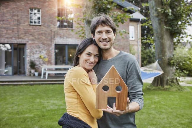 Портрет улыбающейся пары в саду модели своего дома — стоковое фото