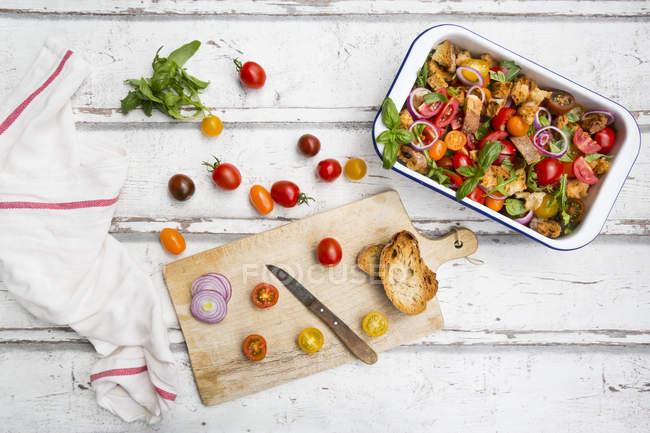 Panzanella hecha de Ciabatta asado, cohete, cebollas rojas, tomates y albahaca - foto de stock