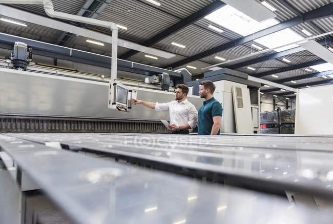 Two men looking at screen on factory shop floor — Stock Photo