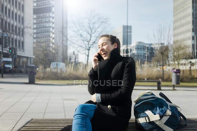 Deutschland, Essen, lachende junge Frau am Telefon sitzend auf der Bank im Freien — Stockfoto