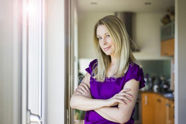 Retrato de mujer madura rubia sonriente en casa - foto de stock