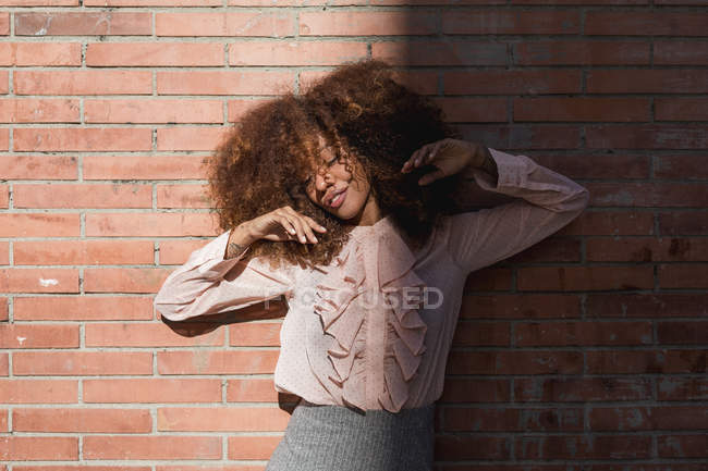 Portrait of beautiful young woman with afro hairdo at brick wall in sunshine — Stock Photo