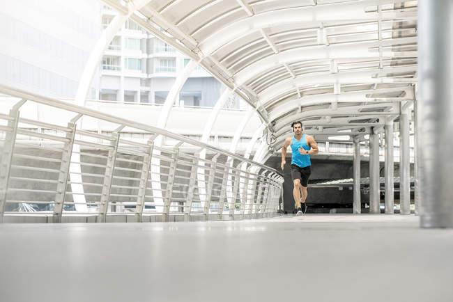 Fit homem correndo na ponte na cidade — Fotografia de Stock