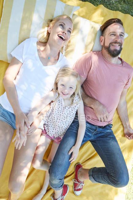 Famiglia felice sdraiata sulla coperta — Foto stock