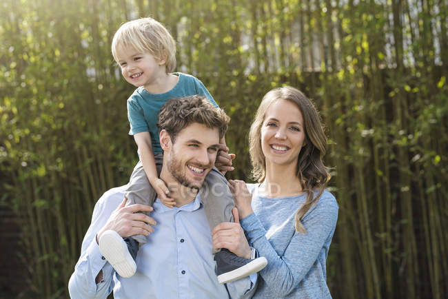 Portrait of happy family in garden in front of bamboo plants — Stock Photo