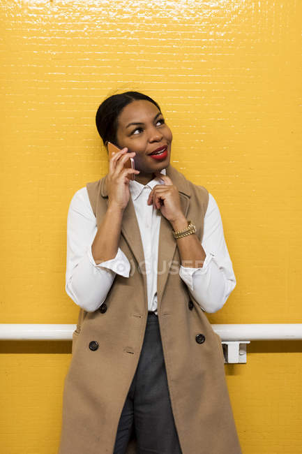 Portrait of smiling businesswoman on the phone standing in front of yellow tiled wall — Stock Photo
