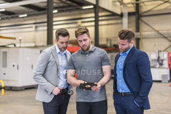 Employee explaining workpiece to businessmen on factory shop floor — Stock Photo