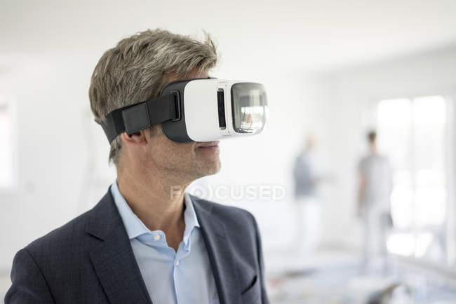 Man in suit wearing VR glasses in building under construction — Stock Photo