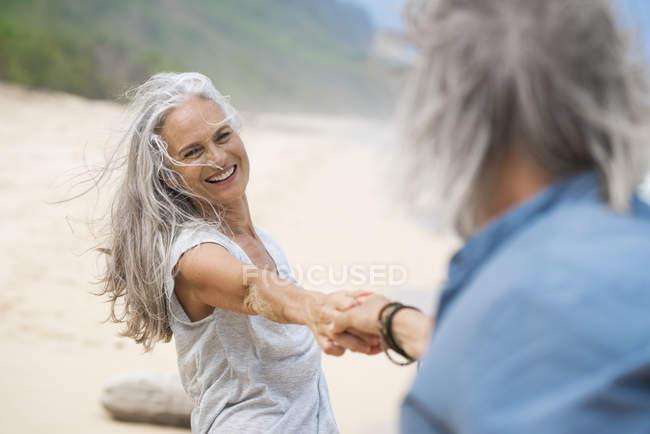 Handsome senior couple dancing on the beach — Stock Photo