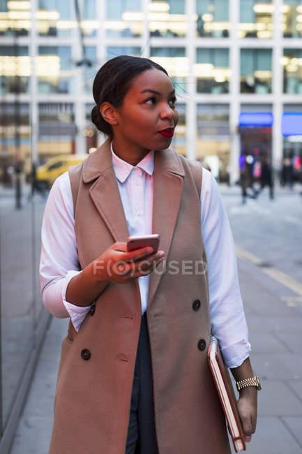 Mujer de negocios sonriente con teléfono celular - foto de stock