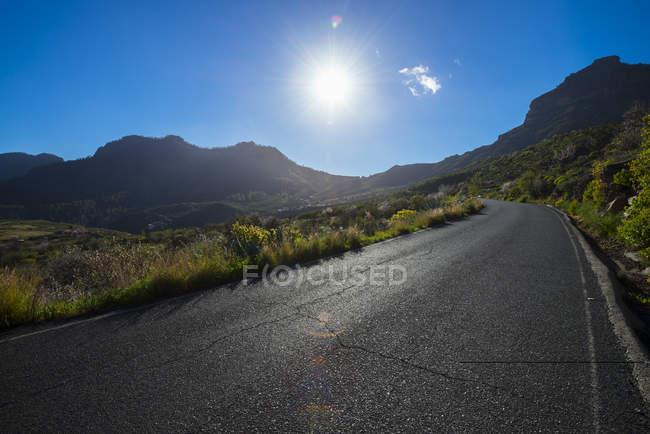 Испания, Канарские острова, Гран-Канария, пустая дорога в лучах солнца — стоковое фото