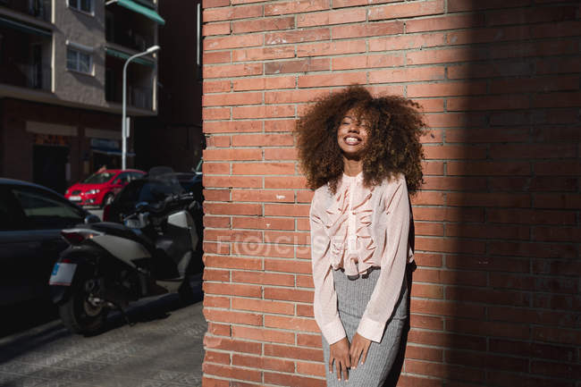 Portrait of smiling young woman with afro hairdo leaning against brick wall in the city — Stock Photo