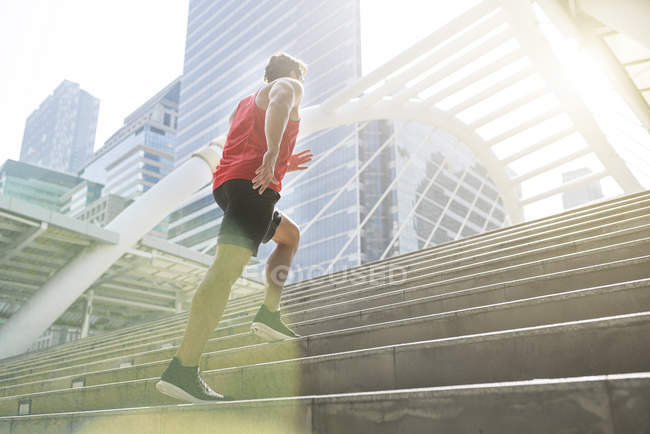 Man in red fitness shirt running upstairs in city — Stock Photo