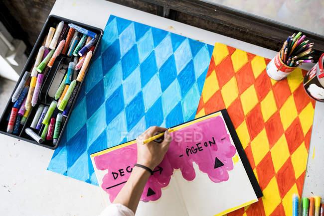 Виконавець малювання в блокнот зі своєю ілюстрацією на столі — стокове фото