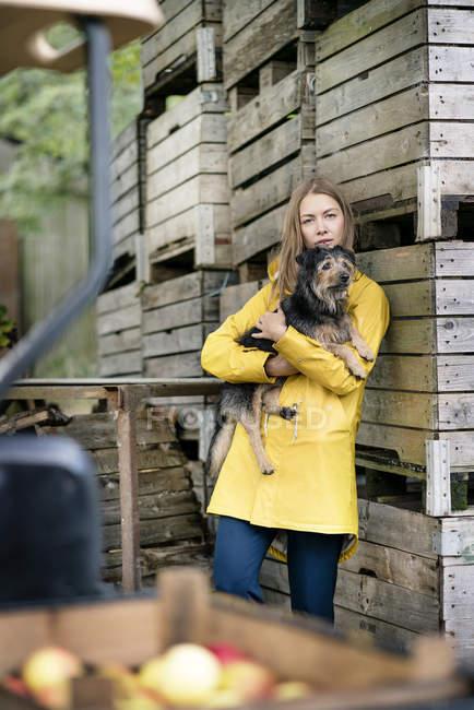 Жінка на фермі стоячи на дерев'яних коробках і тримає собаку — стокове фото