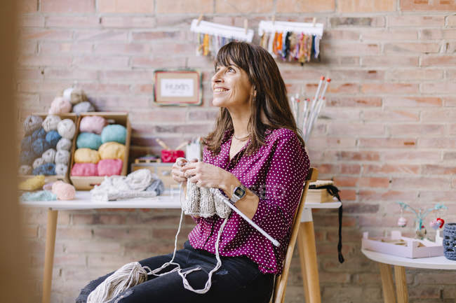 Smiling woman sitting on chair in studio and knitting — Stock Photo