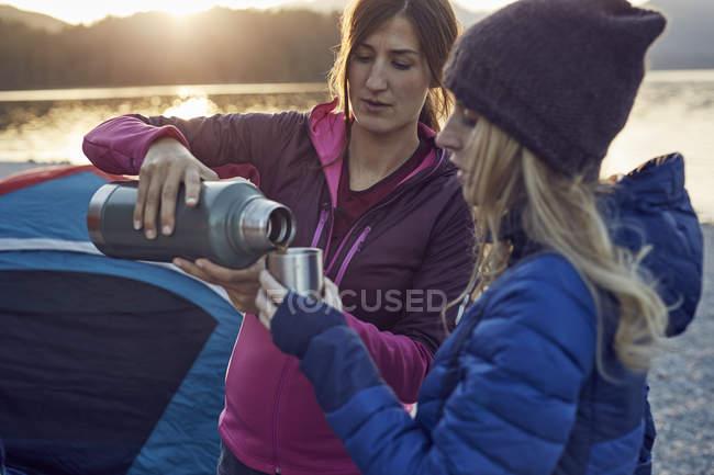 Due donne con bevande calde campeggio a riva al lago — Foto stock