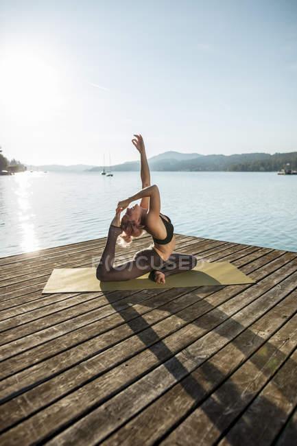 Frau praktiziert Yoga am Steg am See — Stockfoto