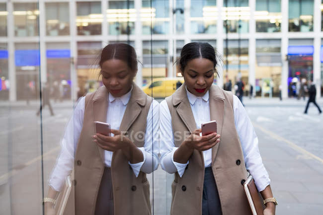 Smiling businesswoman leaning against glass pane looking at cell phone — Stock Photo