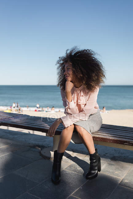 Beautiful young woman with afro hairdo sitting on a bench at the beach — Stock Photo