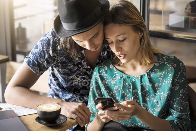 Художественная пара сидит в кафе и проверяет молодую женщину — стоковое фото