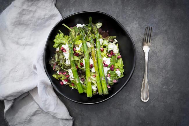 Мікс салат з смаженою зеленою спаржею, фетою і гранатовим насінням — стокове фото
