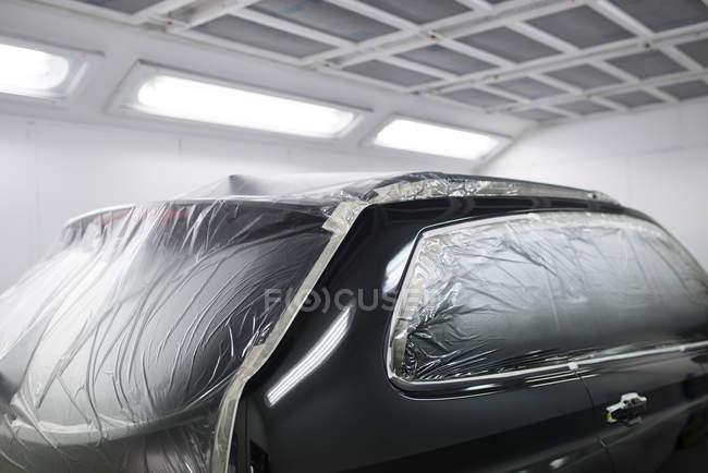 Машина в лакокрасочной кабинке в ремонтном гараже — стоковое фото