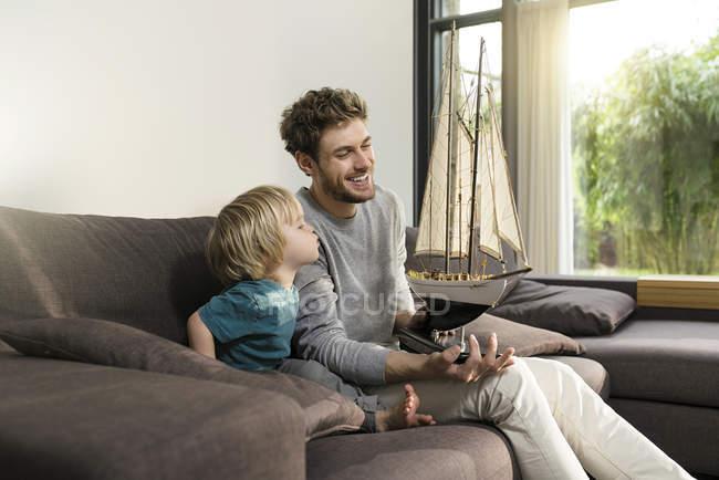 Батько і син з іграшкою модель корабля на дивані будинку — стокове фото