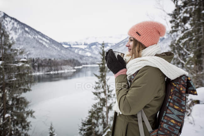 Young woman with hot drink standing in alpine winter landscape with lake — Stock Photo