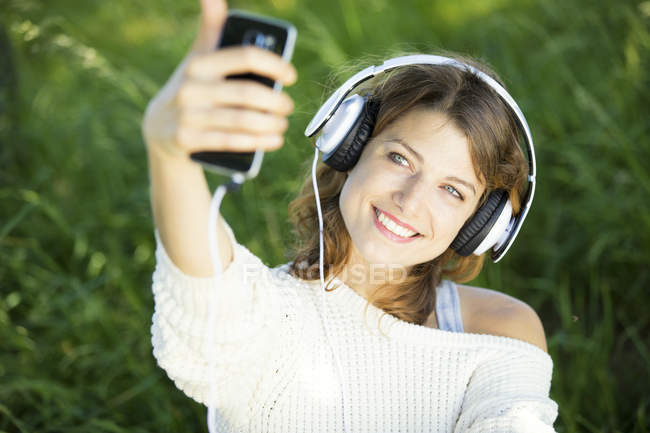 Smiling young woman with earphones taking a selfie — Stock Photo