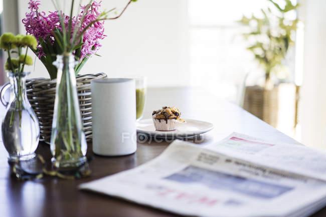 Jornais, vasos de flores, alto-falante e muffin na mesa — Fotografia de Stock