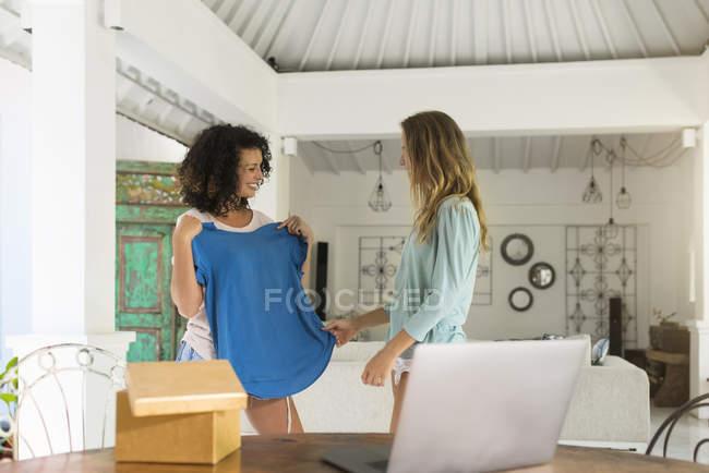 Улыбающаяся женщина показывает новую футболку другу — стоковое фото