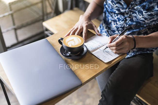 Виконавець пише в блокнот в кафе з кавою і ноутбуком на столі — стокове фото