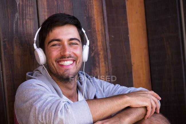 Portrait of happy young man wearing headphones — Stock Photo