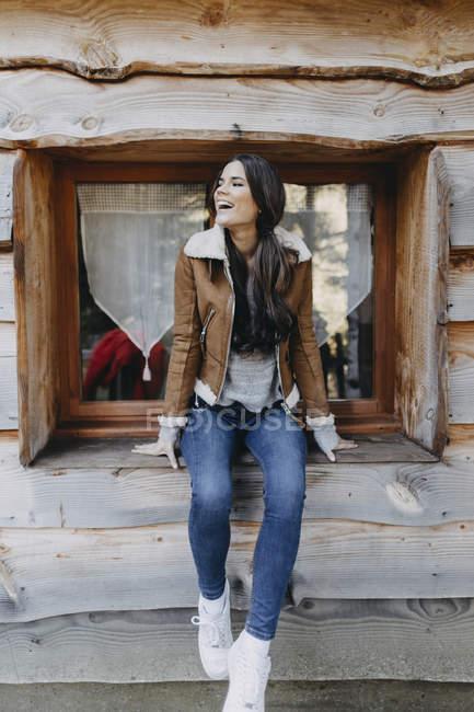Giovane donna felice seduta sul davanzale di una casa di legno — Foto stock