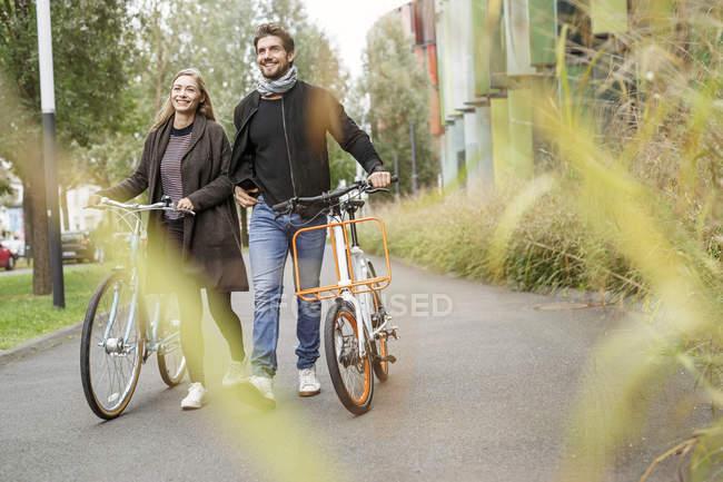 Casal sorridente andando com bicicletas em uma pista — Fotografia de Stock