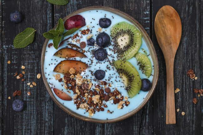 Tazón de batido superalimentario con semillas de chía, arándanos, nectarina, kiwi y granola de chocolate - foto de stock