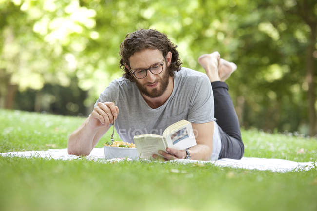 Man reading book on blanket in a park while eating noodle salad — Stock Photo