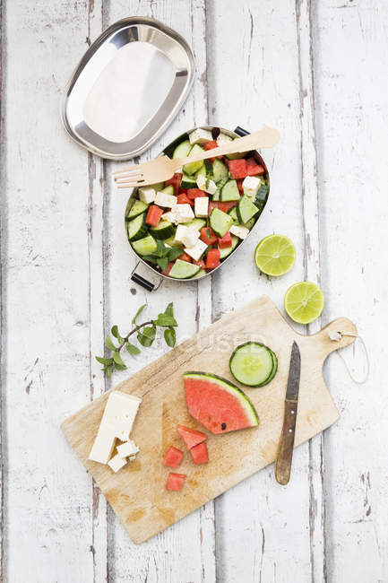 Lunch box, preparation of watermelon salad with feta, cucumber, ment and lime dressing — Stock Photo