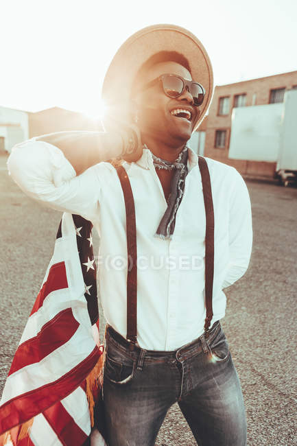 Portrait of laughing young man with American flag at backlight — Stock Photo