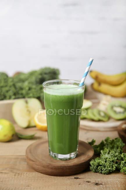 Smoothie verde cercado por ingredientes — Fotografia de Stock