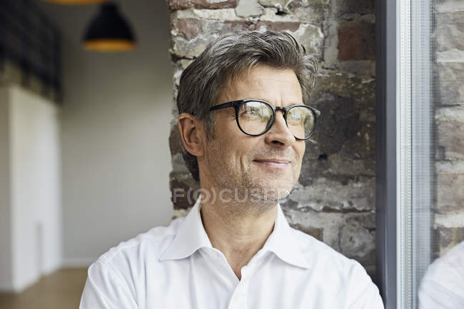 Portrait of smiling businessman wearing glasses and looking out of window — Stock Photo