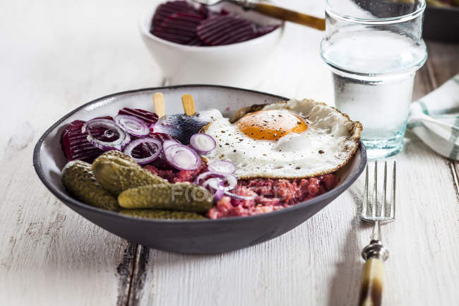 Labskaus, rollmops, pickled gherkin, beetroot salad, onion and fried egg — Stock Photo