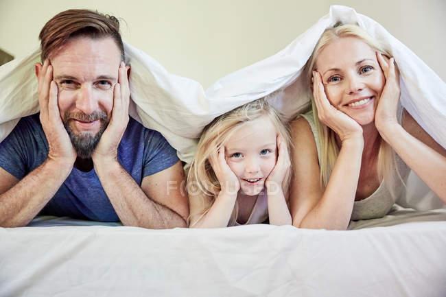 Retrato de familia feliz bajo la manta en la cama - foto de stock