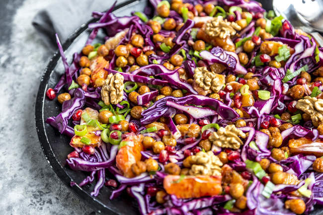 Winter salad, red cabbage, roasted chickpea, blood orange, spring onion and walnut — стоковое фото