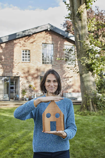 Portrait of smiling woman in garden of her home holding house model — Stock Photo