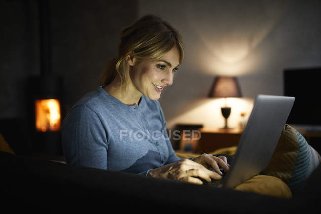 Smiling woman using laptop at home in evening — Stock Photo