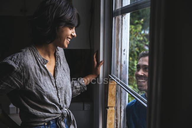 Casal feliz sorrindo um para o outro pela janela — Fotografia de Stock