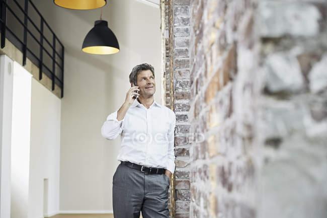 Зрелый бизнесмен, использующий смартфон в современном офисе — стоковое фото